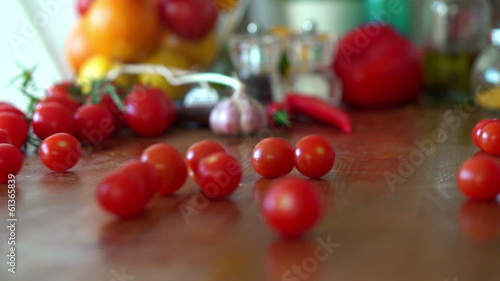 Cherry tomatoes rolling on kitchen table, super slow motion,