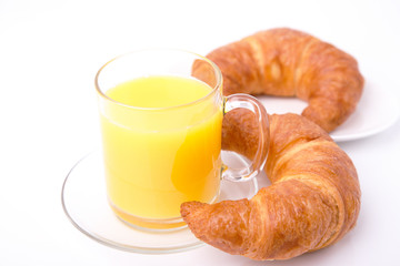 Two croissants on a plate and a cup of juice