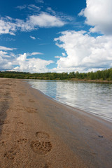 Sandy beach with footprint and forest in Ivalo