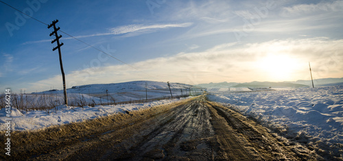 Rural road on a sunset with snow