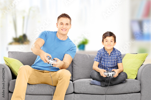 Young man playing video game with his younger cousin