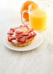 A little glazed strawberry tart and a cup of juice
