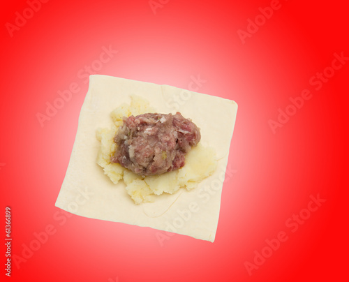 dough with meat on a red background