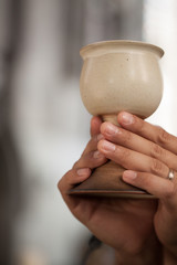 Detail of hands holding chalice with wine in a church.
