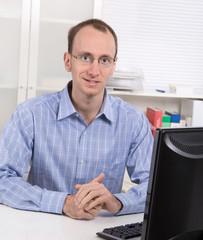 Portrait: Geschäftsmann in Hemd blau sitzend im Büro