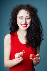 Smiling girl getting out a ring from a red gift box