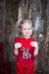 Smiling girl holding heart symbol