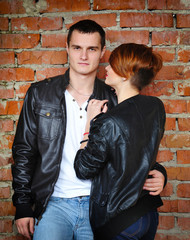 Young enamoured pair on background of red brick wall