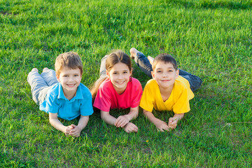 Three smiling kids on the meadow