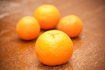 Four ripe orange tangerines closeup photo on wooden table.