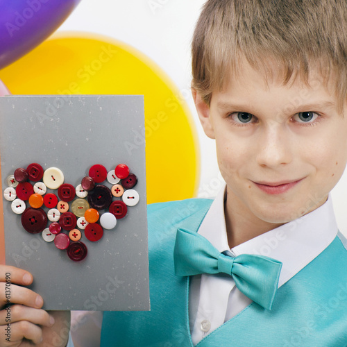 Beautiful child with balloons and postcard of Valentine's Day