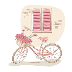 Pink bicycle with basket of flowers near the house wall.