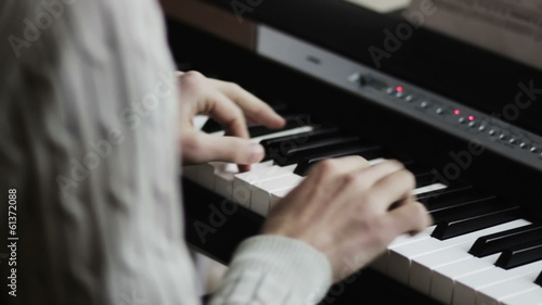 pianist's fingers press the keys on the synthesizer