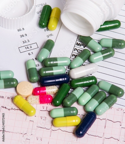 Colorful pills and capsules with analysis background