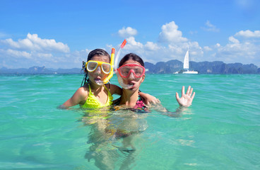 Happy mother and kid snorkeling in tropical sea, family vacation