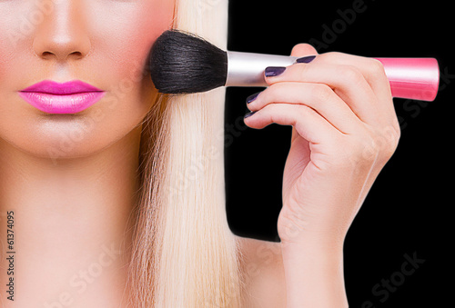 Beautiful girl with makeup brush