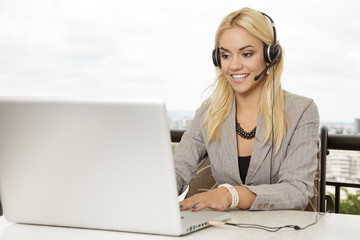 Businesswoman online talking via headset and looking at laptop