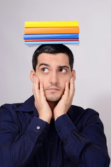 Funny student holding a pile of colorful books on his head.
