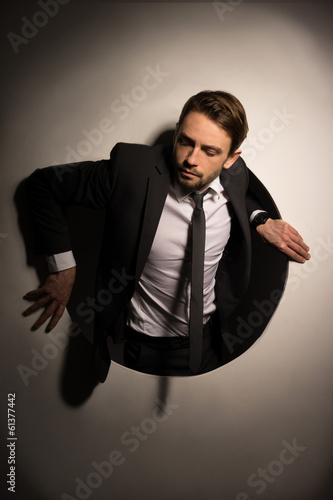 Businessman climbing out of a circular hole