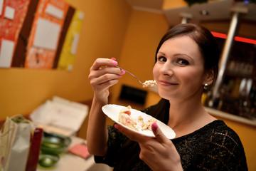 Cheerful woman eating pie
