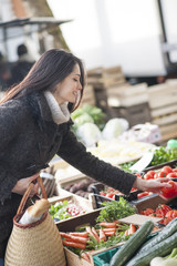 young woman choosing vegetables on a market