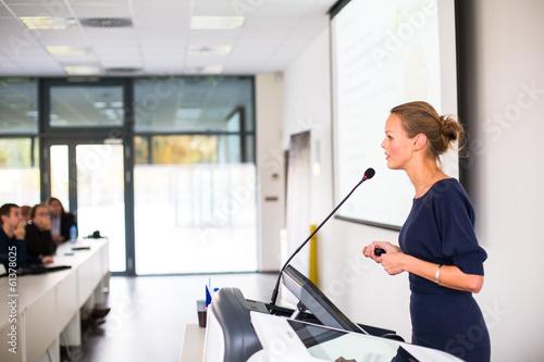 Leinwanddruck Bild Pretty, young business woman giving a presentation