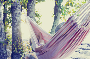 Person relaxing in a hammock, with retro filter effect