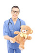 Male healthcare professional in uniform holding a teddy bear