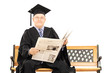 Mature man in graduation gown reading newspaper seated on bench
