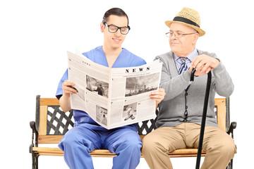 Male nurse reading newspaper to an elderly gentleman
