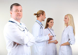 Doctor standing in front of coworkers on grey background