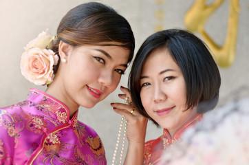 two asian woman wearing a cheongsam