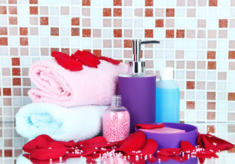 Cosmetics and bath accessories on mosaic tiles background