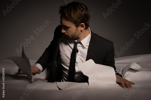 Handsome young bearded businessman climbing out of a hole