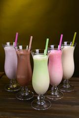 Milk shakes on table on dark yellow background