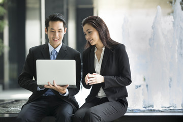 Asian business people working together on a laptop