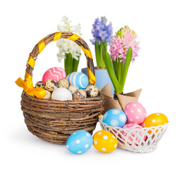 Easter eggs in a basket and spring flowers. White background