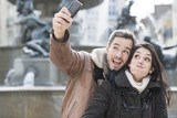 young couple taking a selfie of their grimaces poster