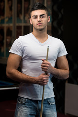 Portrait Of A Young Male Model Playing Billards