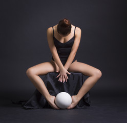 Beautiful gymnast with a ball posing on a black background.