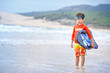 Six years old boy with surf board on exotic beach