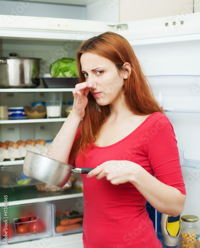 woman  with foul food  near refrigerator