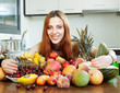 Happy girl with heap of fruits