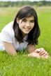 Young teen girl lying on green grass, relaxing