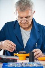 Senior adult Electrician repairing old hair dryer.