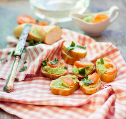 Snack of baguette slices with avocado cream, tomato and onion on