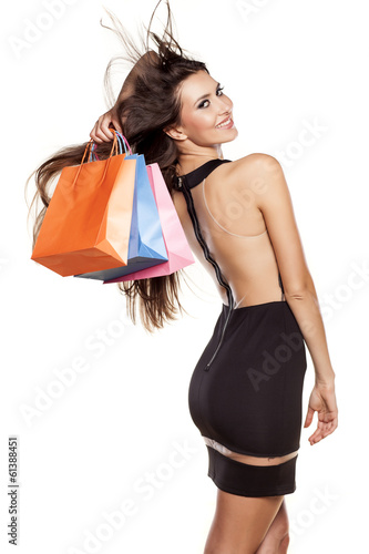 pretty young woman posing with a shopping bags