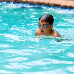 Boy practicing breaststroke in pool.