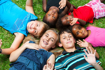 Diverse group og children laying together on grass.