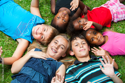 Leinwandbild Motiv Diverse group og children laying together on grass.